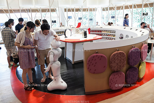 Customers greet the humanoid robot Pepper on its first day as a new member of staff at the NESCAFE coffee-shop in Harajuku on July 11, 2015, Tokyo, Japan. Six robots are programmed to interact with people while introducing the Nescafe products during a special event ''The world? Future cafe by NESCAFE with Pepper'' on Saturday July 11th. The store will continue to employ two robots as regular staff to introduce the shop's products and services. (Photo by Rodrigo Reyes Marin/AFLO)