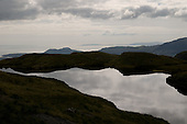 Lake above the Croesor Valley and view towards Porthmadog and the Lleyn Peninsula, Snowdonia National Park.