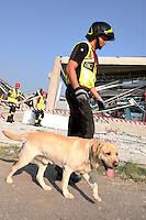 Un vigile del fuoco con un cane di fronte le macerie dell'azienda Haemotronic di Medolla, rasa al suolo dalla scossa di terremoto di ieri 29 maggio 2012, durante le operazioni di recupero del corpo di un operaio disperso, oggi 30 Maggio 2012. ONE SHOT / INSIDEFOTO