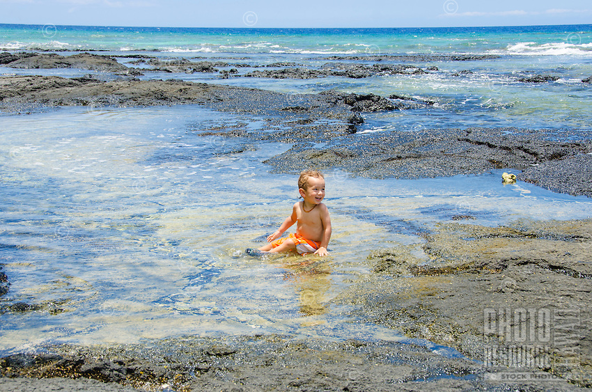 A young local boy laughs as he sits in a tide pool at a beach in Puako, South Kohala, Hawai'i Island.