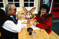 Switzerland. Basel.  Fasnacht Carnival. A couple takes a break, sits on wood benches, eat bread and sausage and drinks coca-cola. A rabbit mask is laid on the table. © 1997 Didier Ruef