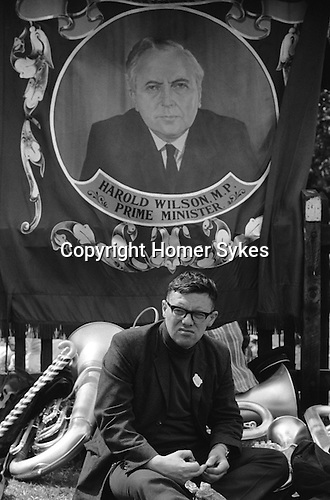 A coal miner sits under a Horden Lodge miner's colliery pit banner depicting a colour portrait of Harold Wilson MP Prime Minister at the annual Durham Miners Gala. County Durham, England 1974.