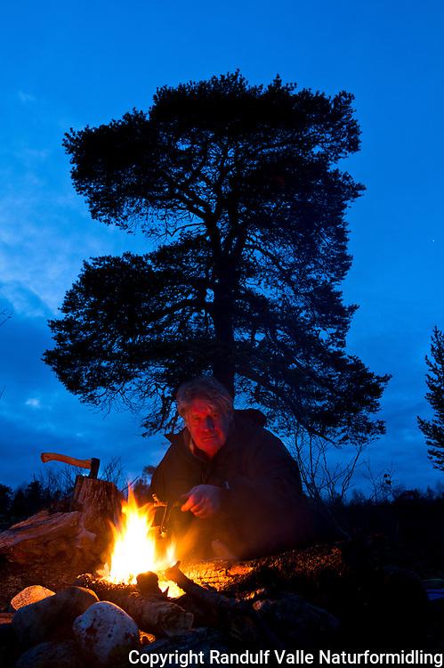 Mann slapper av foran bålet i Øvre Anarjokka Nasjonalpark. ---- Man relaxing in front of camp fire.