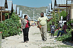 A staff member of the United Methodist Committee on Relief (left), who asked not to be named, walks through the Corail camp for resettled Haitian earthquake survivors with Edisson Laforest, a senior engineer for UMCOR, which has built schools for the community, located north of quake-ravaged Port-au-Prince.