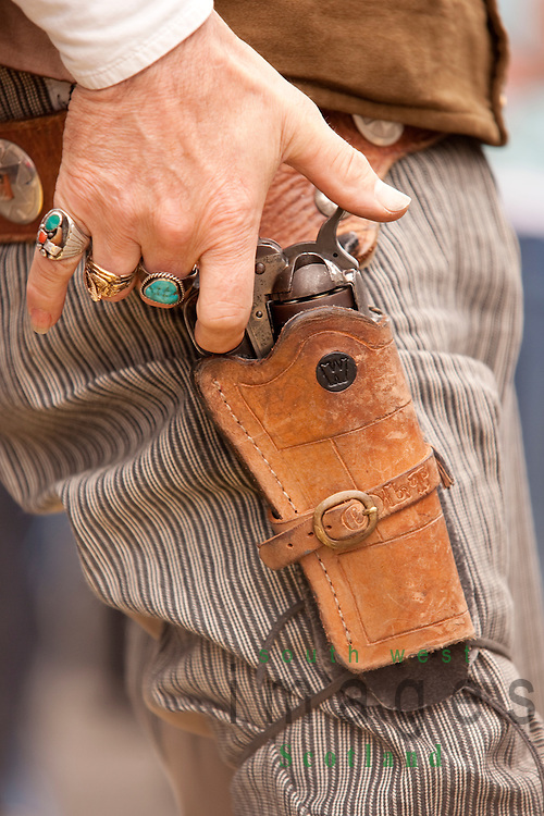 Creetown Country Music Festival, close up photograph of cowboys hand awaiting to draw gun in fastest draw competition. Dumfries and Galloway Scotland UK