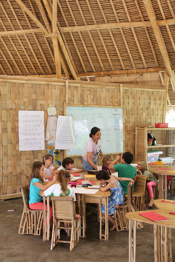 Primary school class. Class agreements are that they will be respectful, work hard, be safe clean and have fun. Everything is made of bamboo or local plants. The Whiteboards are made from recycled windscreens and shockproof glass painted white on the inside.<br /><br />The Green School (Bali) is one of a kind in Indonesia. It is a private, kindergarten to secondary International school located along the Ayung River near Ubud, Bali, Indonesia. The school buildings are of ecologically-sustainable design made primarily of bamboo, also using local grass and mud walls. There are over 600 students coming from over 40 countries with a percentage of scholarships for local Indonesian students.<br /><br />The impressive three-domed &quot;Heart of School Building&quot; is 60 metres long and uses 2500 bamboo poles. The school also utilizes renewable building materials for some of its other needs, and almost everything, even the desks, chairs, some of the clothes and football goal posts are made of bamboo.<br /><br />The educational focus is on ecological sustainability. Subjects taught include English, mathematics and science, including ecology, the environment and sustainability, as well as the creative arts, global perspectives and environmental management. This educational establishment is unlike other international schools in Indonesia. <br /><br />Renewable energy sources, including solar power and hydroelectric vortex, provide over 50% of the energy needs of the school. The school has an organic permaculture system and prepares students to become stewards of the environment. <br /><br />The school was founded by John and Cynthia Hardy in 2008.