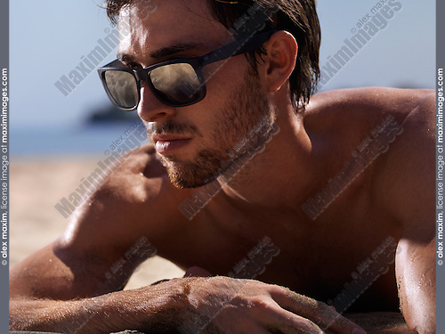 14e1d762642f Expressive closeup portrait of a young man's face wearing sunglasses lying  on sand at the beach