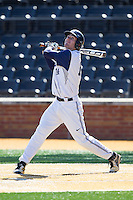 Jake Kuzbel (14) of the Georgetown Hoyas follows through on his swing against the Marshall Thundering Herd at Wake Forest Baseball Park on February 15, 2014 in Winston-Salem, North Carolina.  The Thundering Herd defeated the Hoyas 5-1.  (Brian Westerholt/Four Seam Images)