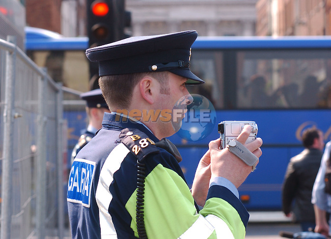 May 1st, 2004. EU Enlargement Day (Day of Welcomes), Dublin, Ireland..A Garda (Irish police) videotapes a peace protest in Dub lin's city centre..Photo:Barry Cronin/Newsfile.