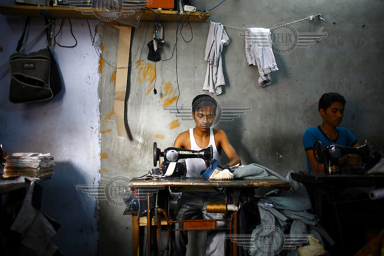 In a small garment factory a worker sews jeans using a foot-powered machine.