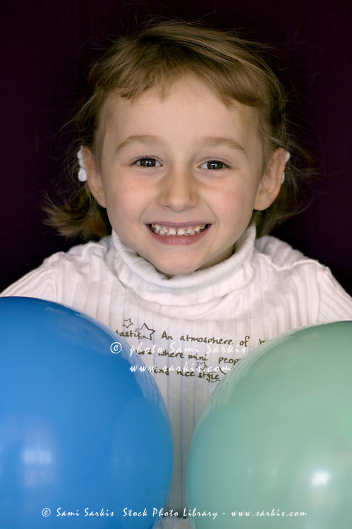 Portrait of a blond girl playing with two balloons.