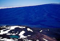 The snow dusted summit of Mauna Loa towers in the background of Waiau Lake on Mauna Kea on the Big Island of Hawaii.