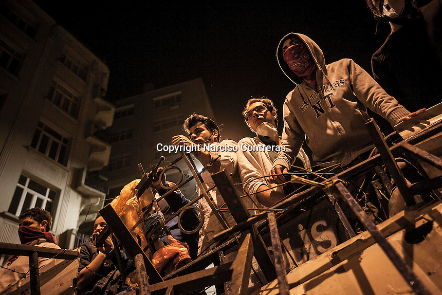 Protesters prepare themselves to clash to the anti-riot police in a barricade at the streets nearby Taksim Square during a masive rally against the turkish government in Istanbul, Turkey.