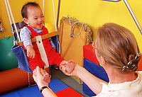 A teaching assistant plays with an infant