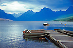 Boats float at a dock on placid scenic Lake McDonald with mountains on a cloudy summer day in Glacier National Park in Montana USA