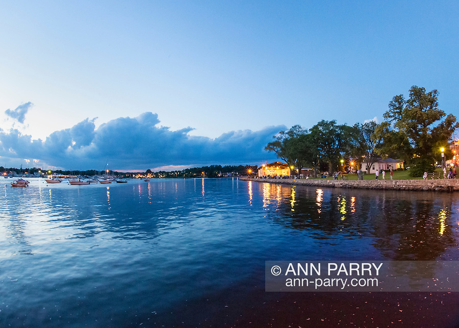 Port Washington, New York, USA. 26th June 2015. Along the shore of Manhasset Bay, at right of vista is waterside Sunset Park with brightly lit John Philips Sousa Memorial Band Shell during a concert, in the North Shore village on Long Island Gold Coast.