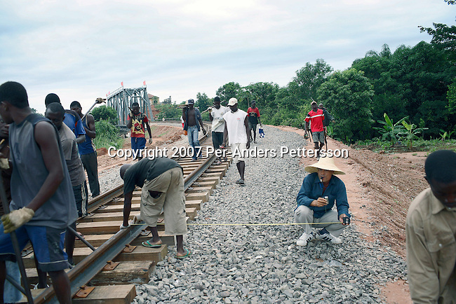 DONDO, ANGOLA APRIL 4: Angolan railway workers adjust the newly put tracks as they are supervised by a Chinese man on April 4, 2007 in Dondo, about 200 kilometers outside Luanda, Angola. Chinese companies are building and upgrading two different railways in Angola, and this part is about 500 kilometers long. All the special equipment has been shipped from China and hundreds of workers live in military style road camps. They are moved as the tracks are laid down. Tens of thousands of Chinese has come to Africa the last years to work in infrastructure projects and businesses. Chinese companies are often the lowest bidders for contracts, pricing out the more expensive European companies. The Chinese people often live where they work and rarely interact with the local population. Most Chinese don't speak English and they are mostly staying in the compounds cooking their Chinese food. (Photo by Per-Anders Pettersson)..
