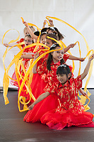 Girls wearing traditional red dresses performing Chinese Ribbon Dance, Northwest Folklife Festival 2016, Seattle Center, Washington, USA.
