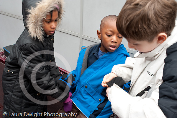 Education Elementary school playground recess Grade 1 boy and girl helping Kindergarten boy with his winter clothing getting mittens on
