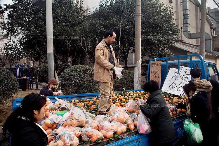 People buy mandarin oranges from a streetvendor on the back of a truck in Nanjing, Jiangsu, China.