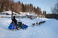 Sebastian Schnuelle runs down the road at Anvik after coming off the Yukon River during Iditarod 2009