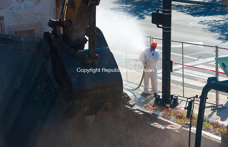 NAUGATUCK, CT-110314JS04-  A worker spares water to keep the dust down as building 25 on Maple Street in Naugatuck, the last major remnant of the U.S. Rubber Company, was demolished on Monday.<br /> Jim Shannon Republican-American