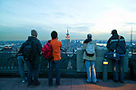 Tourists admiring The View of Manhattan from the Top of the Rock, the observation deck at the top of Rockefeller Center, New York City, NY with a view of the Empire State Building at dusk.