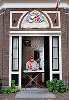 Nederland Alkmaar - 8 oktober 2018.  Alkmaar Ontzet. Man speelt nostalgische muziek in de deuropening van zijn huis. Hij draagt een sjaal van de 8 October Vereeniging.  Foto Berlinda van Dam / Hollandse Hoogte