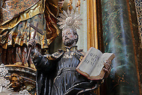 Statue of St Ignatius of Loyola holding cross and open book, 18th century, by Joaquim Bernardes, in the Sao Miguel Chapel, or St Michael's Chapel, designed in Manueline style 1517-22 by Marco Pires and completed by Diogo de Castilho, on the site of a 12th century chapel in the University of Coimbra, Coimbra, Portugal. In the chancel is the Mannerist altarpiece, designed by Bernardo Coelho in 1605 and made by sculptor Simon Mota, with paintings by Simon Rodrigues and Domingos Vieira Serrao. The chapel was renovated in the 17th and 18th centuries, with Manuel Ramos making the pulpit in 1684, ceiling painted by Francisco F de Araujo, tiled floor added 1613, Baroque organ with 2,000 pipes built 1733 by Fray Manuel de Sao Bento, and Gabriel Ferreira da Cunha painting chinoiserie elements in 1737. The University of Coimbra was first founded in 1290 and moved to Coimbra in 1308 and to the royal palace in 1537. The building is listed as a historic monument and a UNESCO World Heritage Site. Picture by Manuel Cohen