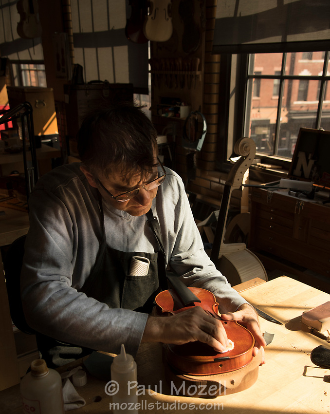 Violin Making & repair Department Head Roman Barnas at the North Bennett Street School in Boston, refinishes an old violin