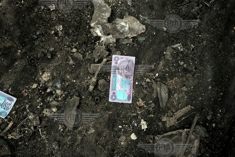 A newly printed old Iraqi Dinar, bearing the image of Sadam Hussein, lies on a street in western Mosul.