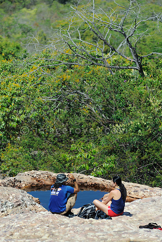 Parque Nacional de Chapada Diamantina, Lencois, Bahia, Brazil: Female tourist with her nature tour guide relaxing at one of many Rio Lencois' natural pools. --- Info: In response to the growing ecotourism in 1985 the Chapada Diamantina National Park (Parque Nacional da Chapada Diamantina) was established as a 1520 sqkm national park approximately 400 kilometres inland from Salvador de Bahia. Today the Chapada Diamantina is recognized as one of Brazil top hiking and outdoor activities destinations. The National Park is a beautiful region comprising of table top mountains, gorges, waterfalls, huge caves and crystalline lakes and bathing pools. Lencois is the main access point to the Chapada Diamantina. --- No signed releases available.