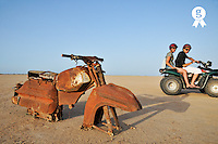 People on ATV by Motorbike wreck in desert (Licence this image exclusively with Getty: http://www.gettyimages.com/detail/106905611 )