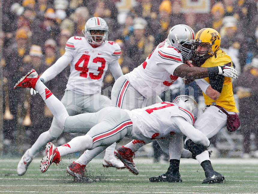 Ohio State Buckeyes defensive lineman Adolphus Washington (92) and Ohio State Buckeyes linebacker Joshua Perry (37) tackle \Minnesota Golden Gophers quarterback Mitch Leidner (7) during the 3rd quarter at TCF Bank Stadium in Minneapolis, Minn. on November 15, 2014.  (Dispatch photo by Kyle Robertson)