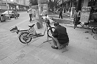 Daytime landscape view of a man repairing an electric bicycle at the B?ij?ng Zhàn in Cháoyáng Q? in Beijing.  © LAN