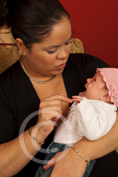 One month old newborn baby girl crying held by mother comforted