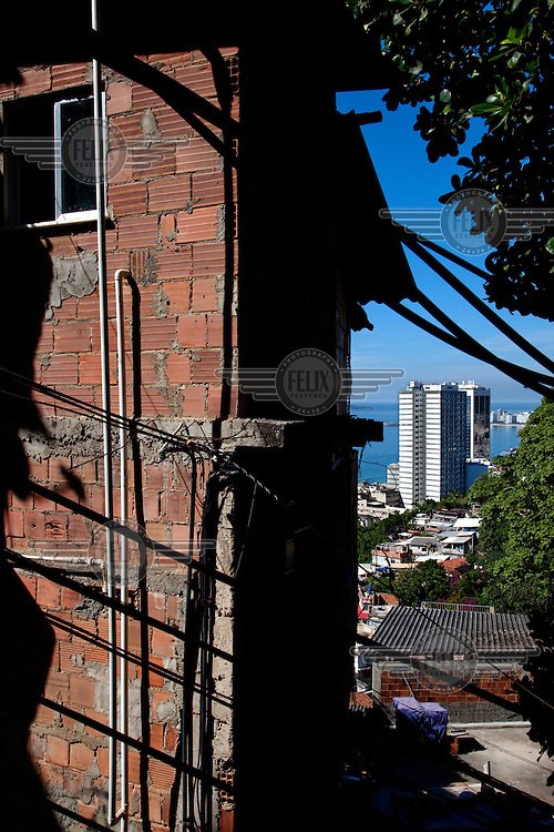 A roughly built house in the Morro da Babilonia favela contrasts with a nearby high rise building.