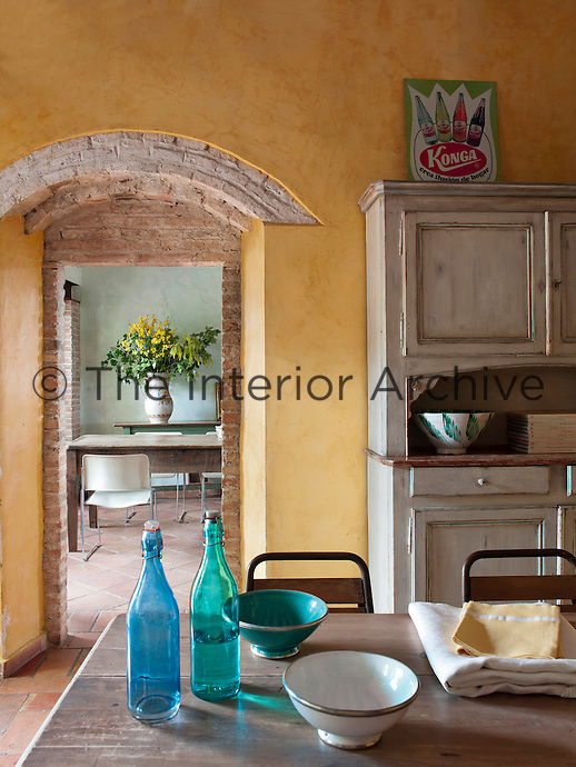 A brick arched doorway leads from the kitchen to the dining room