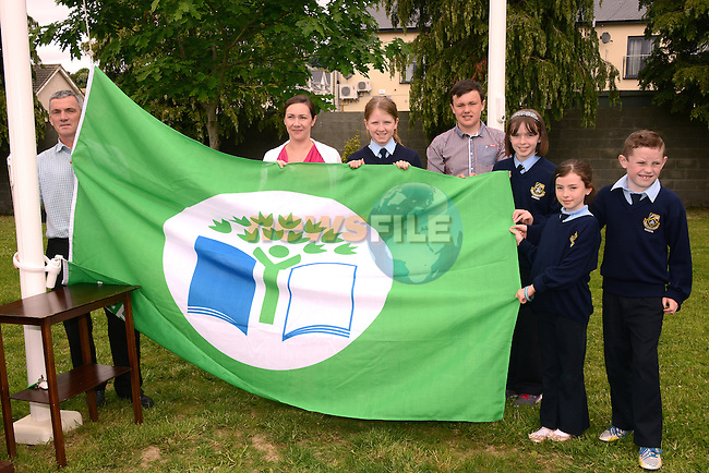 Peter Brady of Meath County Council (left) helps Green School Committee members Darcy Lawlor, Katie Fogarty, Kaitlin Woods, Gearoid Campbell, Conor Nulty and Miss Aine Colgan raise the green flag at Scoil Mhuire National School in Donore.  Photo: Andy Spearman.