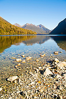 Reflection of Mountains in Lake Gunn, Fiordland, South Island, New Zealand. Lake Gunn is a stunning stop off point on the drive through Fiordland from Queenstown to Milford Sound. In comparison to the crowds of tourists at Milford Sound, Lake Gunn is a very peaceful and often provides stunning reflections of the mountains that surround the lake.