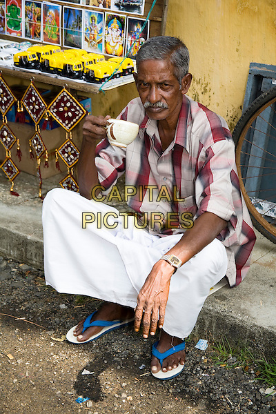 Shopkeeper drinking tea outside a shop, Mattancherry, Cochin, Kerala, India