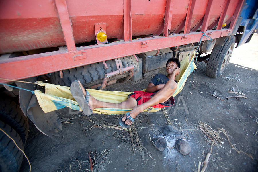 A truck driver talks on his mobile phone as he rests in a hammock that hangs off his truck, which is loaded with sugar cane stalks, at the URSUMCO (Universal Robina Sugar Milling Corporation) cane sugar mill near Bias City on Negros Island, Philippines.