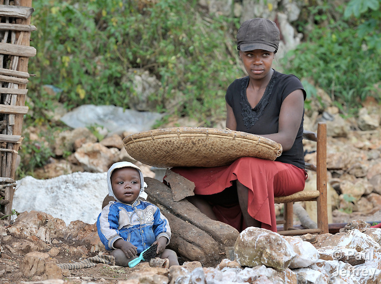 A woman winnows corn in the Haitian village of Foret des Pins while her child looks on.