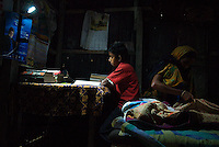 Boy studies in his house with the help of a solar lamp while his mother stitches a katha (katha is used as blanket or bed sheet). Solar lamps are powered with batteries that are in turn charged by solar panels on library boats. The lamps allow poorer villagers to work after dark which helps them increase their income. (Photo by Tadej Znidarcic)