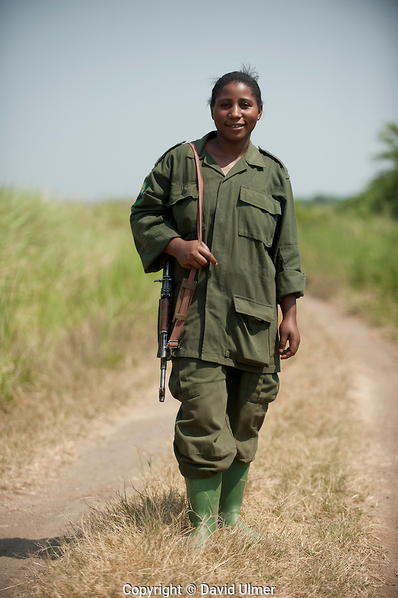 Stephanie, a Uganda Wildlife Authority guide poses in uniform with her AK-47 rifle.
