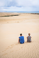 Two tourists at Te Paki Sand Dunes on 90 Mile Beach, Northland, New Zealand