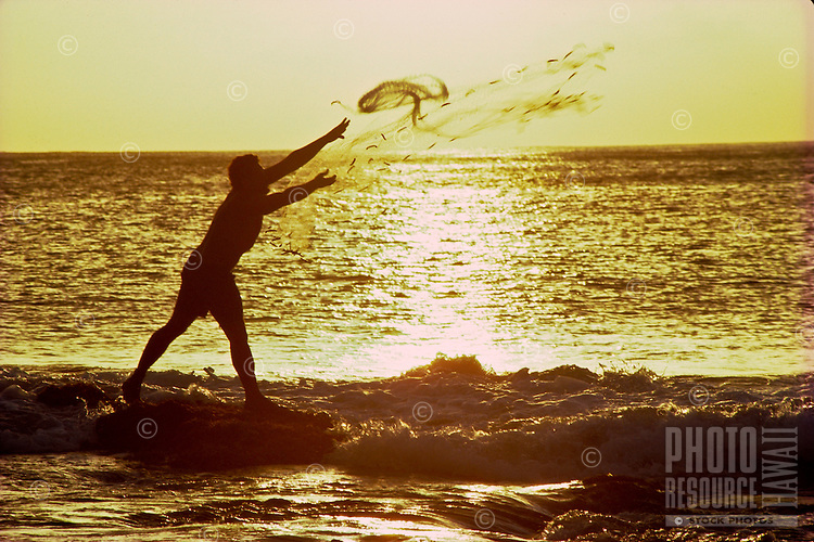 Hawaiian man with throw net fishing at sunset