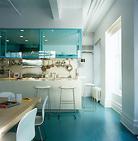 The kitchen at one end of the dining area has pale blue glass shelving and units made from Corian with splashes of stainless steel