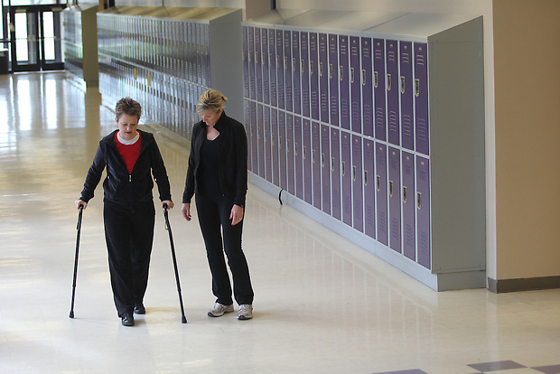 Gayla Tighe uses a pair of canes while walking with friend Glenda Criswell inside Indianola High School. Tighe walks the school's halls three times a week as part of her rehabilitation.  Last July, Gayla suffered a spinal cord injury and was paralyzed.  An accomplished pianist, Gayla has drawn on her faith and made great strides in her rehabiliatation.  Now, some eight months later, she is also beginning to play the piano again.