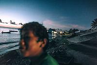 A boy on the shore as dusk falls.